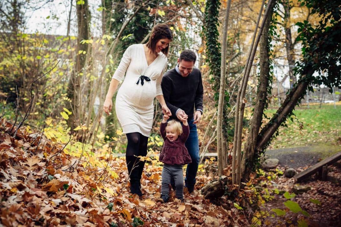 Familie spaziert mit Kind Hand in Hand durchs Laub