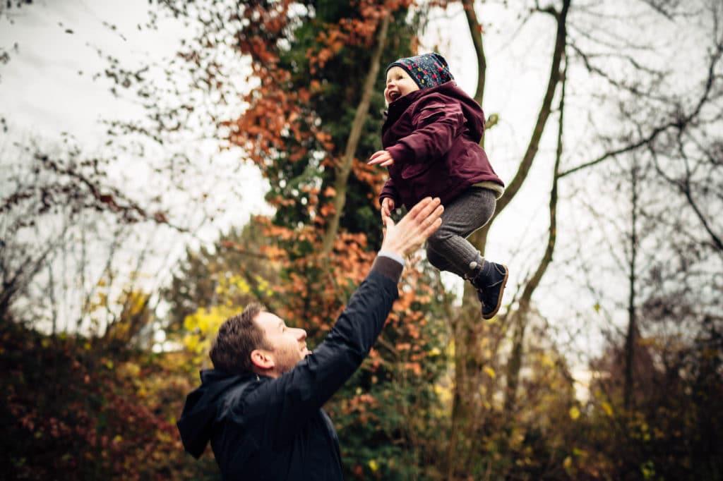 Vater wirft Kind in die Luft und fängt es wieder